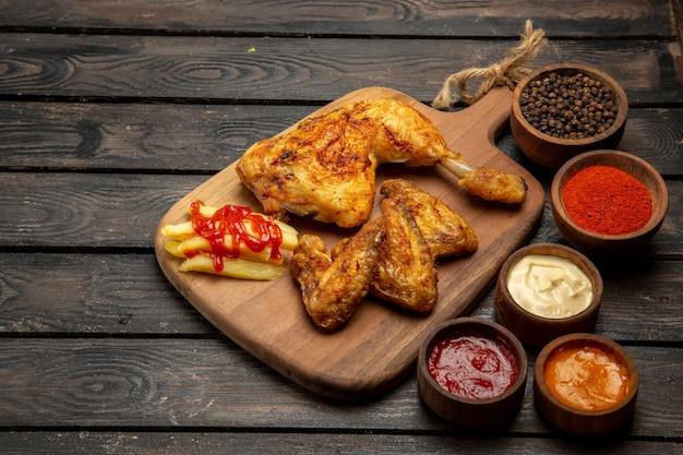 Vista lateral de close-up de frango com asas e coxas de frango apetitosas, batatas fritas e tigelas com molhos coloridos e especiarias na mesa