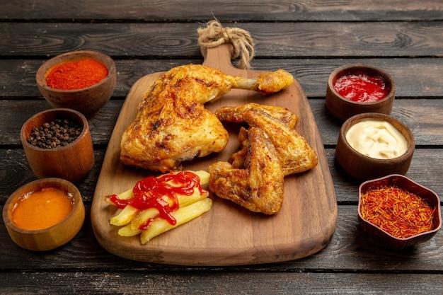 Vista lateral de close-up de frango e especiarias asas de frango e perna de batata frita e ketchup na tábua de cortar entre tigelas de especiarias coloridas e molhos na mesa escura