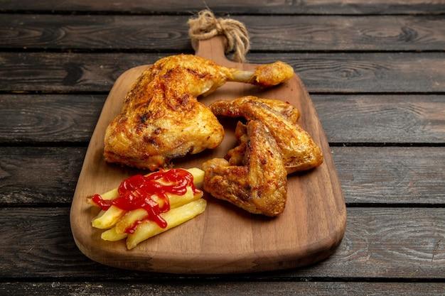 Vista lateral de close-up de frango e especiarias asas e coxas de frango com batatas fritas e ketchup na tábua de corte no centro da mesa escura