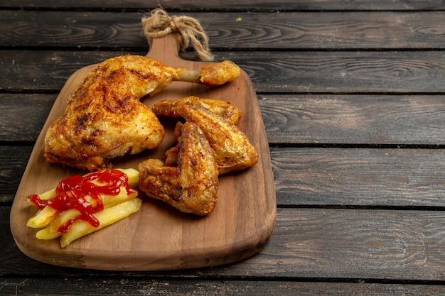Vista lateral de close-up de frango e especiarias asas e coxas de frango com batatas fritas e ketchup na tábua de corte no fundo escuro