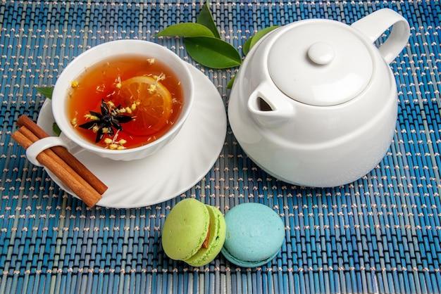 Vista lateral de close-up de macaroons de bule de chá uma xícara de chá em bastões de canela ao lado do bule e macaroons franceses na toalha de mesa branco-azulada