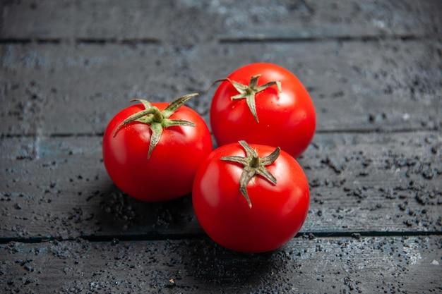 Vista lateral de close-up de tomates na mesa tomates vermelhos na mesa cinza de madeira