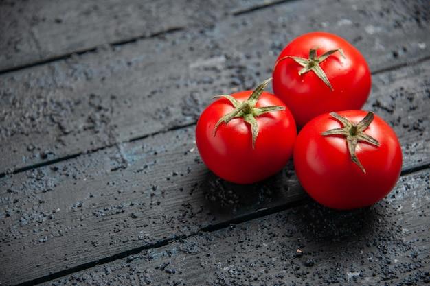 Vista lateral de close-up de tomates na mesa tomates vermelhos no lado direito da mesa cinza de madeira