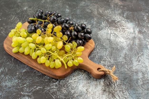 Vista lateral de close-up de uvas, tábua de madeira e cachos de uvas apetitosas
