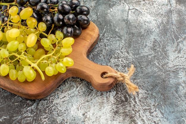 Vista lateral de close-up de uvas, tábua de madeira e uvas verdes e pretas
