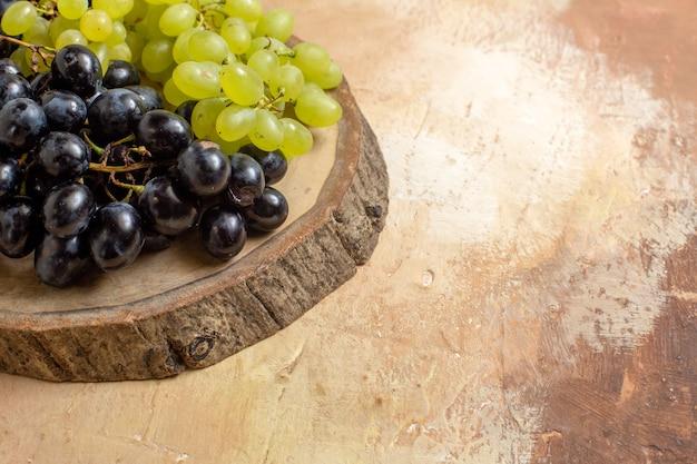 Vista lateral de close-up de uvas uvas pretas e verdes na placa de madeira
