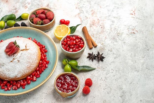 Vista lateral de close-up do bolo de bolo com frutas, limão, canela, anis estrelado, nas tigelas