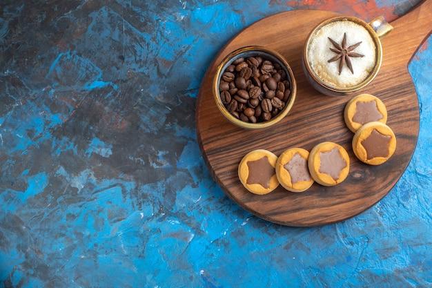 Vista lateral de close-up doces biscoitos grãos de café uma xícara de café na placa de madeira