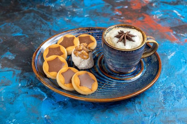 Vista lateral de close-up doces, biscoitos, manjar turco e uma xícara de café no prato azul