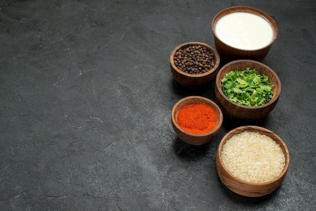 Vista lateral de close-up em pratos de especiarias coloridas de ervas de especiarias coloridas, arroz com creme de leite e pimenta do reino no lado direito da mesa de madeira