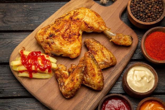 Vista lateral de close-up em tigelas de frango e temperos com molhos e temperos e frango e batatas fritas na tábua de corte