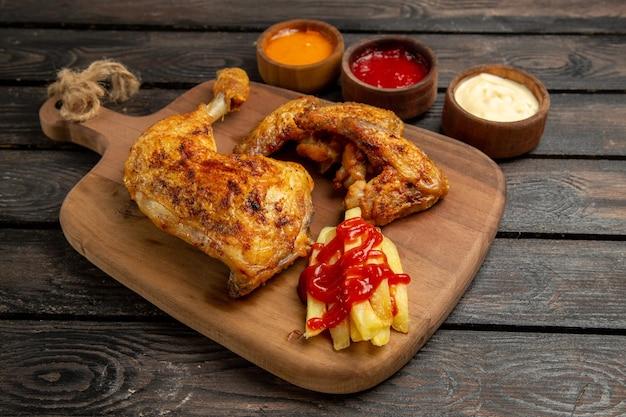 Vista lateral de close-up em tigelas de frango e temperos de três tipos de molhos ao lado das asas e coxas de frango com batatas fritas e ketchup na tábua de corte no fundo escuro