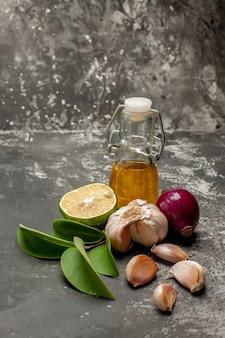 Vista lateral de close-up especiarias cebola limão folhas alho e garrafa de óleo na mesa