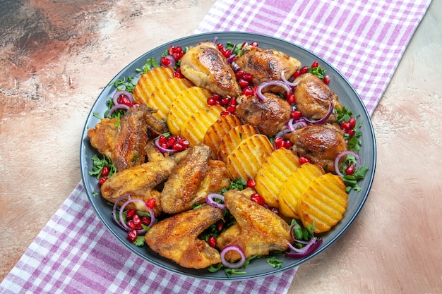 Vista lateral de close-up frango prato de frango, batata, ervas, cebola na toalha de mesa
