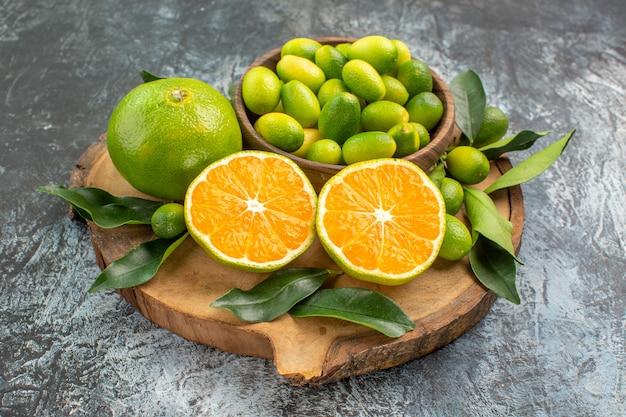 Vista lateral de close-up frutas cítricas as frutas cítricas apetitosas com folhas na placa de madeira