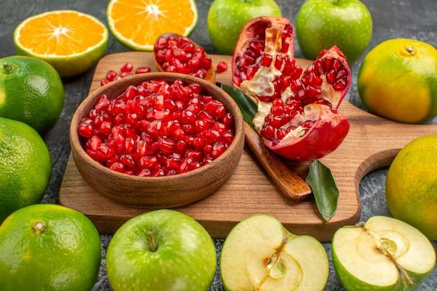 Vista lateral de close-up frutas cítricas sementes de romã no quadro maçãs tangerinas