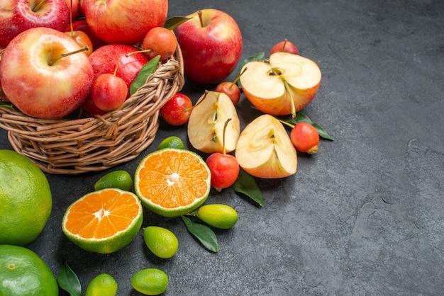 Vista lateral de close-up frutas frutas bagas na cesta ao lado de diferentes frutas