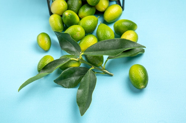 Vista lateral de close-up frutas frutas verdes-amarelas com folhas na cesta cinza sobre a mesa azul