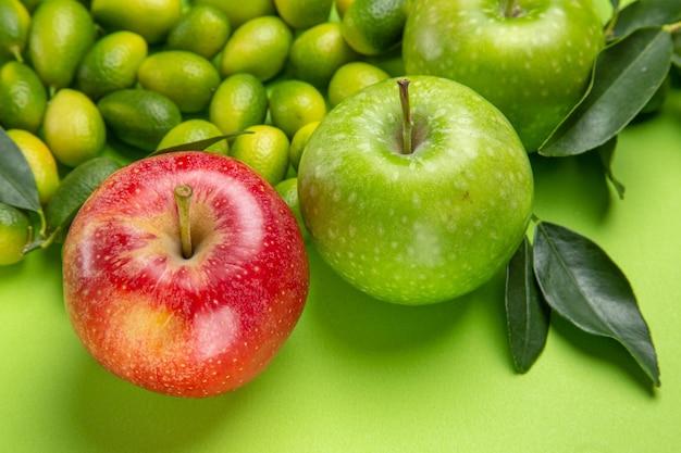 Vista lateral de close-up frutas maçãs vermelhas e verdes frutas cítricas com folhas