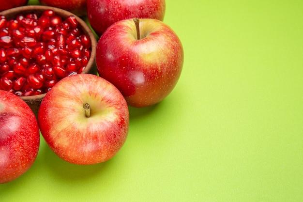 Vista lateral de close-up frutas maçãs vermelhas tigela de sementes apetitosas de romã na mesa