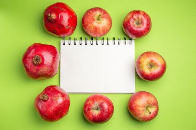 Vista lateral de close-up frutas, romãs, maçãs ao redor do caderno branco sobre o fundo verde