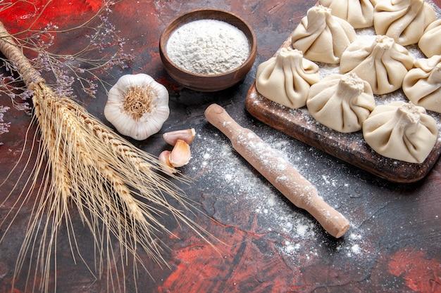 Vista lateral de close-up khinkali khinkali no tabuleiro farinha rolo espigas de trigo alho