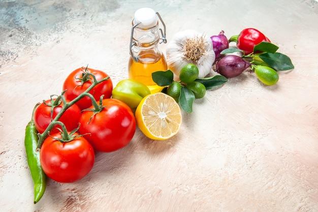 Vista lateral de close-up legumes cebola alho pimenta pimenta limão tomate óleo pimentão