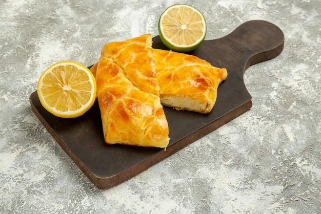 Vista lateral de close-up limão e lima limão e tortas apetitosas na tábua de corte no centro da mesa