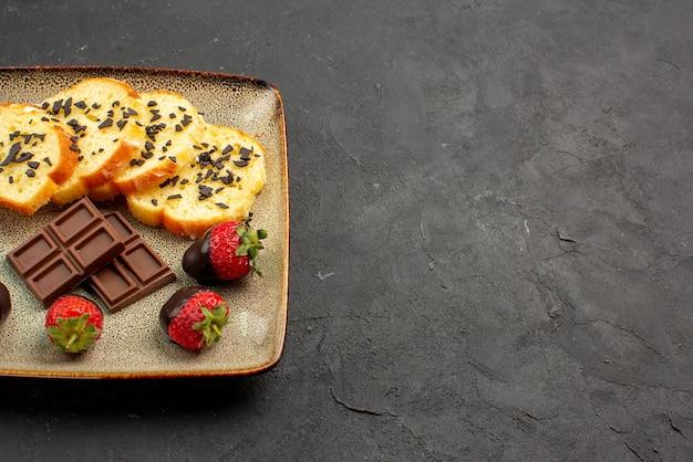 Vista lateral de close-up morangos e bolo de morango coberto com chocolate e bolo com chocolate no lado esquerdo da mesa