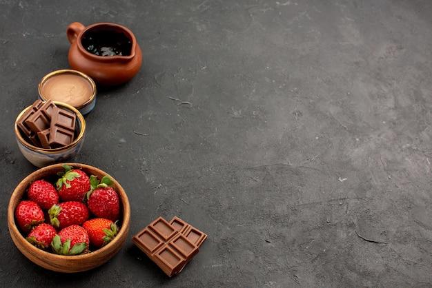 Vista lateral de close-up, morangos, morangos e creme de chocolate em tigelas e barras de chocolate no lado esquerdo da mesa escura
