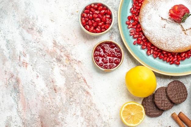 Vista lateral de close-up o apetitoso bolo biscoitos de limão geleia de canela uma xícara de chá e o bolo