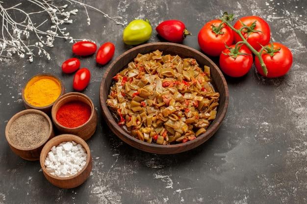 Vista lateral de close-up prato apetitoso feijão verde e tomate na placa de madeira ao lado dos tomates com pedicelos e tigelas de especiarias coloridas na mesa escura