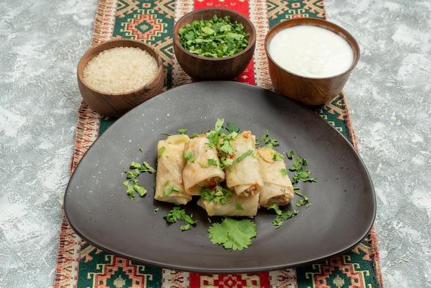 Vista lateral de close-up prato apetitoso prato de repolho recheado com ervas de arroz e creme de leite em uma toalha de mesa colorida com padrões no centro da mesa
