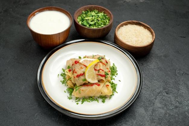 Vista lateral de close-up prato apetitoso repolho recheado com ervas de limão e molho no prato branco e tigelas com ervas de creme de leite e arroz no centro da mesa preta
