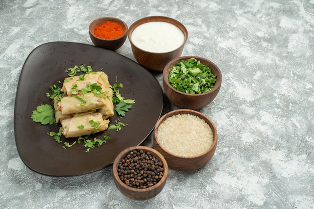 Vista lateral de close-up prato com especiarias recheado de repolho no prato ao lado da tigela com especiarias creme de leite, ervas, arroz e pimenta preta no lado esquerdo da mesa