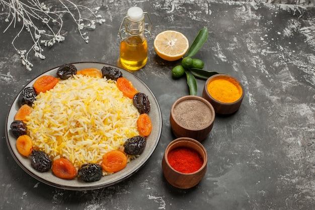 Vista lateral de close-up prato de arroz com arroz com frutas secas especiarias garrafa de óleo de frutas cítricas