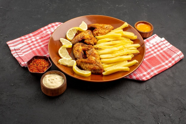 Vista lateral de close-up prato de fastfood apetitosas asas de frango batatas fritas com limão e tigelas de molhos e especiarias em uma toalha de mesa quadriculada rosa-branca na mesa preta