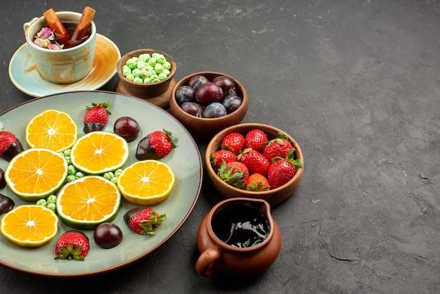 Vista lateral de close-up prato de frutas cobertas de chocolate, doces de morango verde, laranja picada e tigelas de calda de chocolate e frutas vermelhas no lado esquerdo da mesa