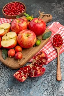 Vista lateral de close-up romã colher de romã maçãs cerejas na placa de madeira