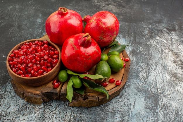 Vista lateral de close-up romãs apetitosas romã vermelha com folhas na tábua de madeira