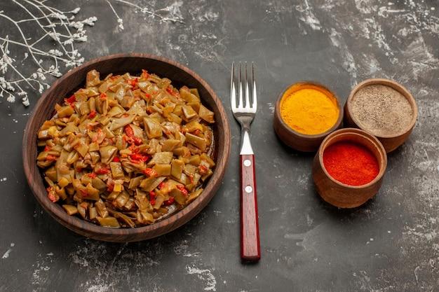 Vista lateral de close-up temperos e prato prato marrom de feijão verde e tomate e garfo na mesa escura