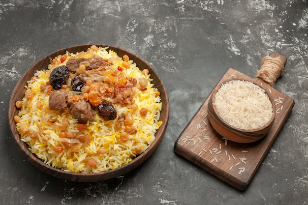 Vista lateral de close-up tigela de arroz com especiarias na tábua pilaf na tábua