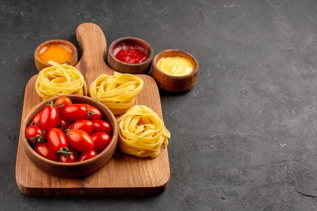Vista lateral de close-up tomates e macarrão tomate e macarrão na mesa da cozinha ao lado das tigelas de molhos na mesa