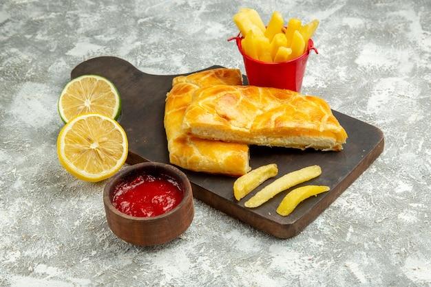 Vista lateral de close-up tortas batatas fritas tigela de ketchup, limão e batatas fritas e tortas apetitosas na placa da cozinha na mesa cinza