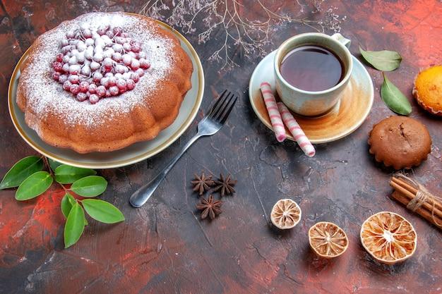 Vista lateral de close-up um bolo um bolo com frutas vermelhas, paus de canela, cupcakes, uma xícara de chá, frutas cítricas