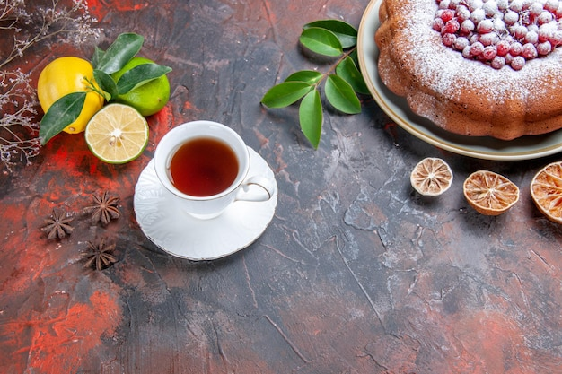 Vista lateral de close-up um bolo um bolo com groselha e frutas cítricas uma xícara de chá de anis estrelado