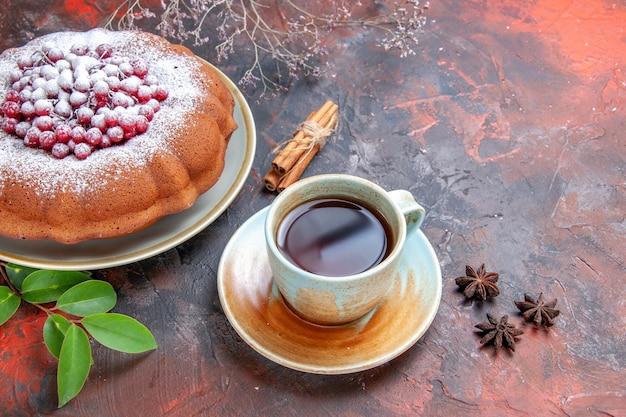 Vista lateral de close-up um bolo uma xícara de chá de anis estrelado um bolo apetitoso com frutas silvestres açúcar de confeiteiro
