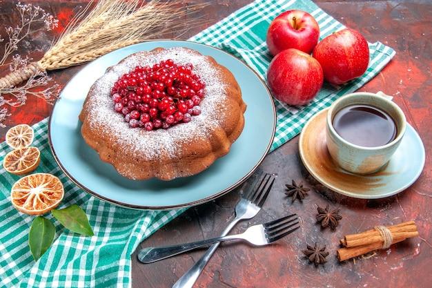 Vista lateral de close-up um bolo uma xícara de chá garfos um bolo três maçãs na toalha de mesa espigas de trigo