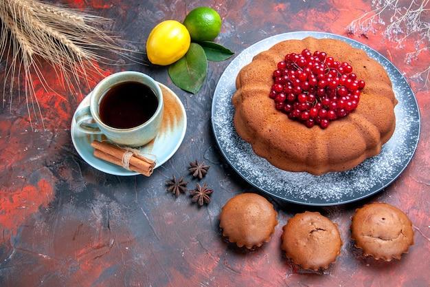 Vista lateral de close-up uma xícara de chá um apetitoso bolo cupcakes frutas cítricas uma xícara de chá anis estrelado