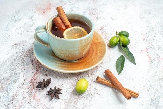 Vista lateral de close-up uma xícara de chá uma xícara de chá com limão e canela no pires com frutas cítricas anis estrelado e paus de canela na mesa